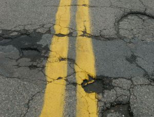 a badly damaged road that may cause an accident