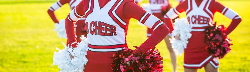 Three cheerleaders in red and white uniforms standing with pom poms on their hips
