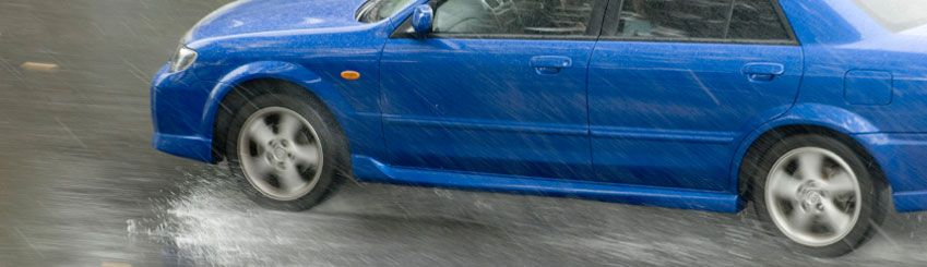 A blue motor vehicle skidding across a water covered road
