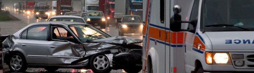 A silver car that has been smashed after an accident that damaged the passenger side doors and rear bumper, with an ambulance in the foreground.