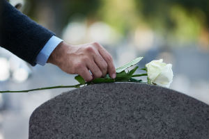 man placing flower on a grave