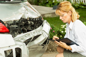 insurance claims adjuster inspecting damaged car